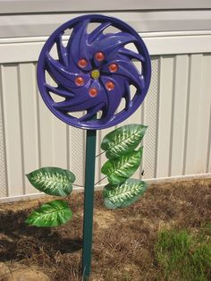 Hubcap flower #1. Mom painted it purple, I made the yellow beaded center and red glitter circles.