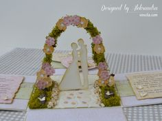 Wedding exploding box with married couple under the floral arch.
