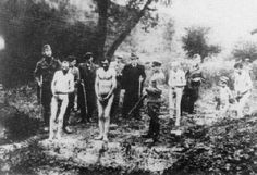 Jewish men stand at the edge of a mass grave in Nazi occupied Russia, waiting to be shot.  Behind, more other men, and a young boy, wait their turn.  The Nazis forced the Jews to strip as a form of degradation, and because it made escape more difficult.  Also, their clothing was cleaned and sent to Germany for sale to Germans down on their luck.  Note the well-dressed civilians observing the executions as if they were a carnival attraction.