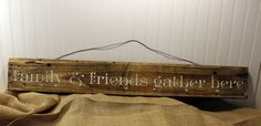 """Family and Friends Gather Here Wall Art from Reclaimed Pallet Wood 40x6, White Lettering on Bare Wood. The warm atmosphere of home when friends and family are gathered captured in this single plank pallet wood sign. Complete with rustic wire for hanging. Sealed for indoor or outdoor use. 40x6 Every design is intentionally distressed and sealed to be used indoors or outdoors. The measurements for each item may vary within 1-2"""" of the listing size - depending on the wood that can be sourced…"""