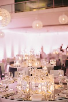 A formal white wedding reception with mirrored centerpieces | @ashleysawtelle1 | Brides.com
