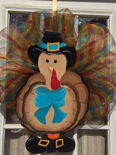 Hand painted multi-colored turkey. Lots of personality! Mesh half wreath accenting tail feathers.