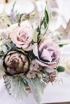 Pale purple centerpieces with artichokes and roses