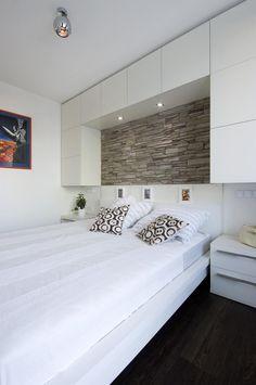 Úložný prostor nad postelí je využíván jako šatní skříně, které by jinak zbytečně zabíraly podlahovou plochu. Vestavěné osvětlení dokonale nahrazuje stolní nebo nástěnné lampy na čtení a majitel tak opět šetří místem. Koláž na zdi je dárek od sestry – autorky.