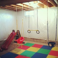 Indoor swing set! Cost Under $300. Foam flooring from Lowes, half bucket swing and hardware from Home Depot, slide from toys r us, infant swing from Meijer, trapeze from Walmart.  This idea has given my kids a way to exert energy on rainy days, hot days and during the cold winters!!
