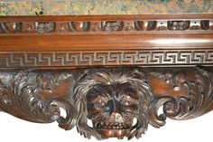 "Detail ~ 19thC Irish Chippendale Center Table ~ A wonderfully carved Irish Chippendale mahogany center hall table (or server), the long sides centered with large growling lions heads below greek key and egg and dart moldings; the four legs with shell carving to the tops, tapering to large hairy paw feet; topped with a wonderful 'green pink' marble slab; Irish mid-19thC.     Dimensions: (marble 44"" x 24""), table height 32.5"" / Three Centuries Shop"