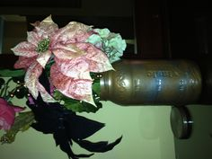 I spray-painted a large pickle jar using a copper color and a silver color. I then inserted some random flowers purchased from Michael's.