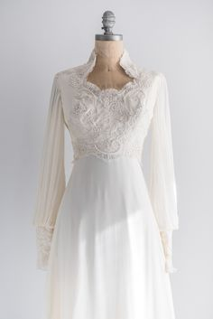Late 1970s gown with lace alencon applique bodice, long poet sleeves with cuffed wrists. Skirt is a slight empire with pleated trims and slight train.
