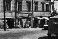 Hertankatu 13. Puutalo, jonka kivijalassa Jalkinekorjaamo - Skoreparation. Ovella romaninainen. Oikealla lihakauppa, kyltissä teksti Lihaa-Kött. 1970