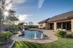 A covered patio leads to a well-landscaped pool with fountains. Newly built homes in the Regency at Carrara Estates community by K. Hovnanian Homes in Gilbert, AZ.