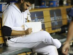 Tigers' J.D. Martinez (28) takes notes after striking