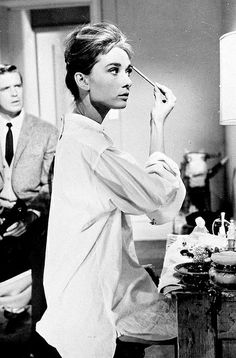 "George Peppard and Audrey Hepburn in Blake Edward's film of Truman Capote's novelette ""Breakfast At Tiffany's"": Holly doing her eyes."