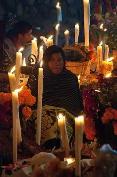 Mujer alumbra con velas al anochecer / NOCHE DE MUERTOS EN JANITZIO
