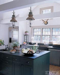 The kitchen of a Long Island weekend house features cabinets by Richard Ward Baxter Restorations, GE Monogram appliances, and soapstone countertops; the pendant lights are retrofitted 19th-century industrial gas lamps.     Photographer: William Waldron   Designer: Geoffrey Ross and John Dransfield