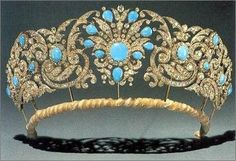 We'll call this the Teck Turquoise Tiara because it shares provenance with both the Teck Crescent Tiara and the Teck Circle Tiara: they all come from Queen Mary's mother Princess Mary Adelaide, the Duchess of Teck. This particular piece was made around 1850 and is composed of diamonds and turquoise stones set in a central sunburst motif surrounded by rococo scrolls.