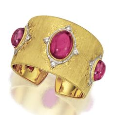 18 KARAT GOLD, RUBELLITE AND DIAMOND BANGLE-BRACELET, BUCCELLATI The hinged cuff of satin-finished gold set with 3 oval cabochon rubellites, and 12 round diamonds weighing approximately 1.00 carats, set within white gold frames, mounted in 18 karat white and yellow gold, signed M. Buccellati, Italy.
