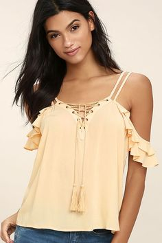 We've been dreaming of the True Love's Kiss Peach Lace-Up Top! Woven rayon falls from two sets of skinny straps, into a breezy, bodice framed by fluttering off-the-shoulder sleeves. Lace-up neckline features brass grommets and tasseled ties.