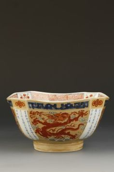"AN UNUSUAL OCTAGONAL DRAGON BOWL, the exterior enamelled with four dragons in iron red on a cafe-au-lait ground, the corner panels with calligraphy in underglaze blue, the base with a six character Kangxi mark within a double circle, 7"" across"