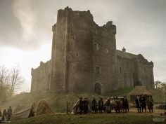 This new photo released today shows us what Doune Castle looks like Outlander-fied as Castle Leoch with villagers and highlanders out front. The morning light and the slight mist/fog gives it an eerie and historical feel.   Castle Leoch Doune