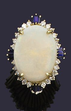 An opal, sapphire and diamond dress ring The large oval cabochon opal, within a brilliant-cut diamond border, accented at intervals with trefoils of tapered baguette-cut sapphires, to bifurcated shoulders, finger size L