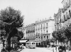 Murcia, Arenal y Glorieta de España c.1957 . Al fondo el Café Moderno, derribado poco después para abrir la Gran Vía. La casa de la derecha fue adquirida y demolida en los 60 por el Banco Coca (luego absorvido por el Banco Español de Crédito), en los años 80, la oficina pasó a ser una de las principales sucursales de la entidad en la ciudad junto a la central ubicada en la calle Trapería (en el edificio que diseñara a comienzos de los años 30 el arquitecto Pedro Muguruza)