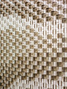 Drift, a sculptural artwork for the lobby of the Kempinski Hotel, Dubai by Giles Miller Studio.   Thousands of boxes of varying depths are suspended in front of a wall and lit in such a way that they cast varying degrees of shadow on the wall behind.