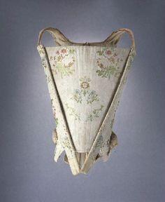 Corps à baleines ouvert avec un devant d'estomac amovible en taffetas écru façonné et broché de fils polychromes, motif placé de bouquets de roses tandis que le dos est en toile de lin rose passé. Le devant d'estomac et le bord du décolleté sont doublés d'une indienne à fond écru et d'une toile de coton écrue peinte de rinceaux fleuris, les côtés et le dos sont doublés d'une toile de lin ou de coton écru. La forme du corps et les étoffes employées indiquent une datation vers 1750-1760