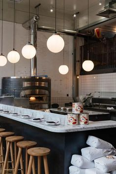 Radio Alice Shoreditch. Italian pizza restaurant in London with white marble high bench to watch open kitchen