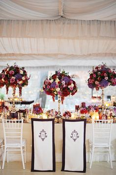 The bride and groom's seats at the head table are marked with monogrammed chair covers.