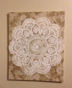 Just using old things that were in a closet, or drawer. I glued scrapbook paper on a canvas art board, put a couple of coats of modge podge on the paper and let it dry. Then just glued the doily on the board. Simple, easy, and I love it!