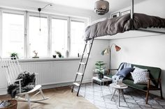 A raised double bed in a bedroom / sitting room. Clever small space style in…