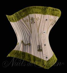 """Corset en coutil rose 1890' de marque """"LEOUZON"""" évantaillé et brodé de petites fleurs, orné de velours chenille vert olive sur le haut et en bas, gorge baleinée, doublé et comportant 44 baleines - Busc de 32 cm avec 4 attaches - Tour de taille 52 cm. Collection Nuits de Satin"""