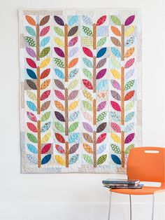 """Summer Leaf features colorful, patterned leaves on brown stems across the length of the quilt. This scrappy quilt is great practice in sewing curved pieces. Learn how to make the """"pie 'n' crust"""" quilt block in a free video tutorial. Digital pattern available!"""