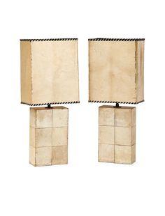 Jacques ADNET (1900-1984) Paire de lampes, corps parallélépipédique vertical gainé de larges bandes de parchemin formant motif de damier, hampe de laiton soutenant la douille, abat-jour parallélépipédique en parchemin bordé d'un laçage de cuir noir. Haut. 55,4 cm - Larg. 22 cm - Prof. 14,5 cm