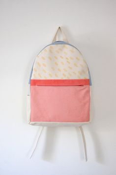 natural canvas backpack with pink, blue, bright red-orange, and pale yellow canvas accents. adjustable straps,  brass hardware,  heavy-weight canvas,  1
