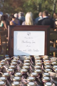 blackberry jam jars as double duty  favors and escort cards line up on table. Wedding gifts at Hamptons wedding in the Summer