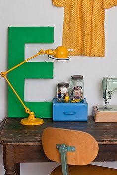 Love this retro yellow lamp and old wooden desk!
