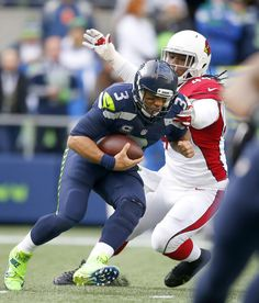 Russell Wilson Photos Photos - Linebacker Markus Golden #44 of the Arizona Cardinals takes down quarterback Russell Wilson #3 of the Seattle Seahawks at CenturyLink Field on December 24, 2016 in Seattle, Washington. - Arizona Cardinals v Seattle Seahawks