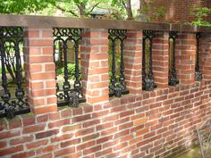 "Repurposed wrought iron porch sections now ""windows"" in our brick fence."