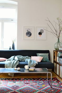 Cozy living room with a dark couch, some pillows in pastel colors, a colorful carpet and a metal coffee table.