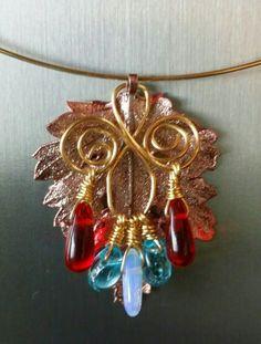 Hoja natural con proceso de metalizado en oro color rosado con gotas de cristal rojo, azul y opalo