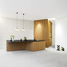 This new apartment building completed in 2015, is located in Gartenstrasse, Central Berlin, Germany, and was designed by Bruzkus Batek Architekten. With a blend of light concrete floors, stark white walls, raw-colored wood paneling, and an amazing countertop in matte black, this modern design is a space perfectly illuminated by the natural light that enters through the glass doors located in one of the walls of the room. In the..