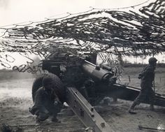 Two American soldiers next to a howitzer with netting, in a Signal Corps photograph