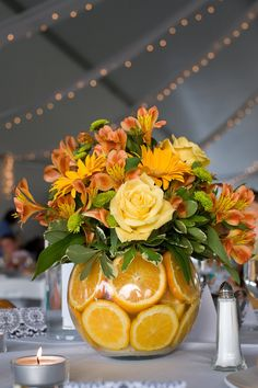 Wedding Flower Arrangements With yellow roses and marigold gerbera daisies topping a vase filled with orange slices, this bright centerpieces brings energy to the table. - Amp up your table's focal point with fresh goodness. Fruit Centerpieces, Wedding Centerpieces, Wedding Table, Centrepiece Ideas, Vase Ideas, Wedding Rustic, Trendy Wedding, Graduation Centerpiece, Quinceanera Centerpieces