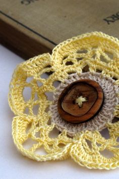 This is an original design flower brooch crocheted with 100% mercerized cotton crochet thread, and finished in the center with a decorative