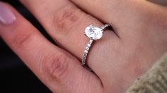 Oval solitaire with a diamond band.