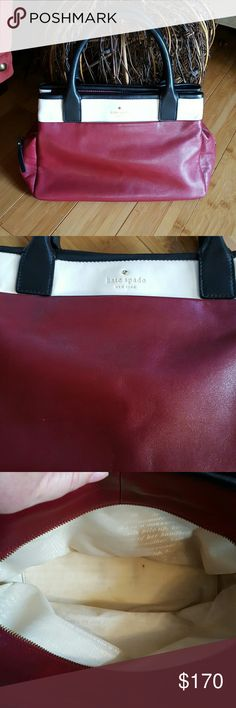 LAST DAY!  Gorgeous Kate Spade Leather Handbag Not sure I want to part with this one! Deep red with white and black trim and signature leather bow detail on bottom. This is preloved but in great condition. Small mark on front left (pic 2). Inside, a couple of small marks on the lining of the middle section. The other 2 sections are perfect!  3 sections, 2 with magnetic closure and center with zipper.  Bag has just been professionally cleaned in and out and leather conditioned. 13in x 8.5 in…
