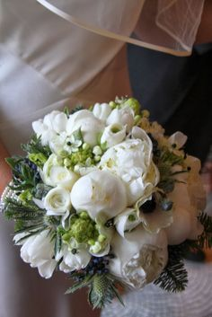 White Wedding Bouquet included White Winter Peonies, Ranunculas, Roses, Tulips, Eryngium Thistles, Black Viburnum Tinus Berries, Anemones, Freesia, Eucalyptus Boules and lots of lovely Winter Evergreens