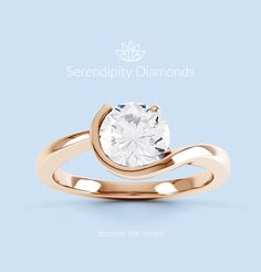 Orion. A beautifully modern, round diamond solitaire engagement ring, shown here in 18ct rose gold, with a combination setting and unique flowing design. From Serendipity Diamonds. #discoverthedream #engagementring