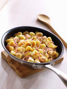Epluchez et hachez l'oignon, faites-le revenir dans une grande poêle avec l'huile d'olive, l'ail et le romarin, ajoutez les gnocchis poursuivez la cuisson 5 à 8 minutes. Ajoutez le râpé de jambon. Fouettez les jaunes d'œufs avec le mascarpone, le zeste du citron et le jus. Nappez les gnocchis et faites chauffer à feu doux 1 à 2 minutes. Servez sans attendre.